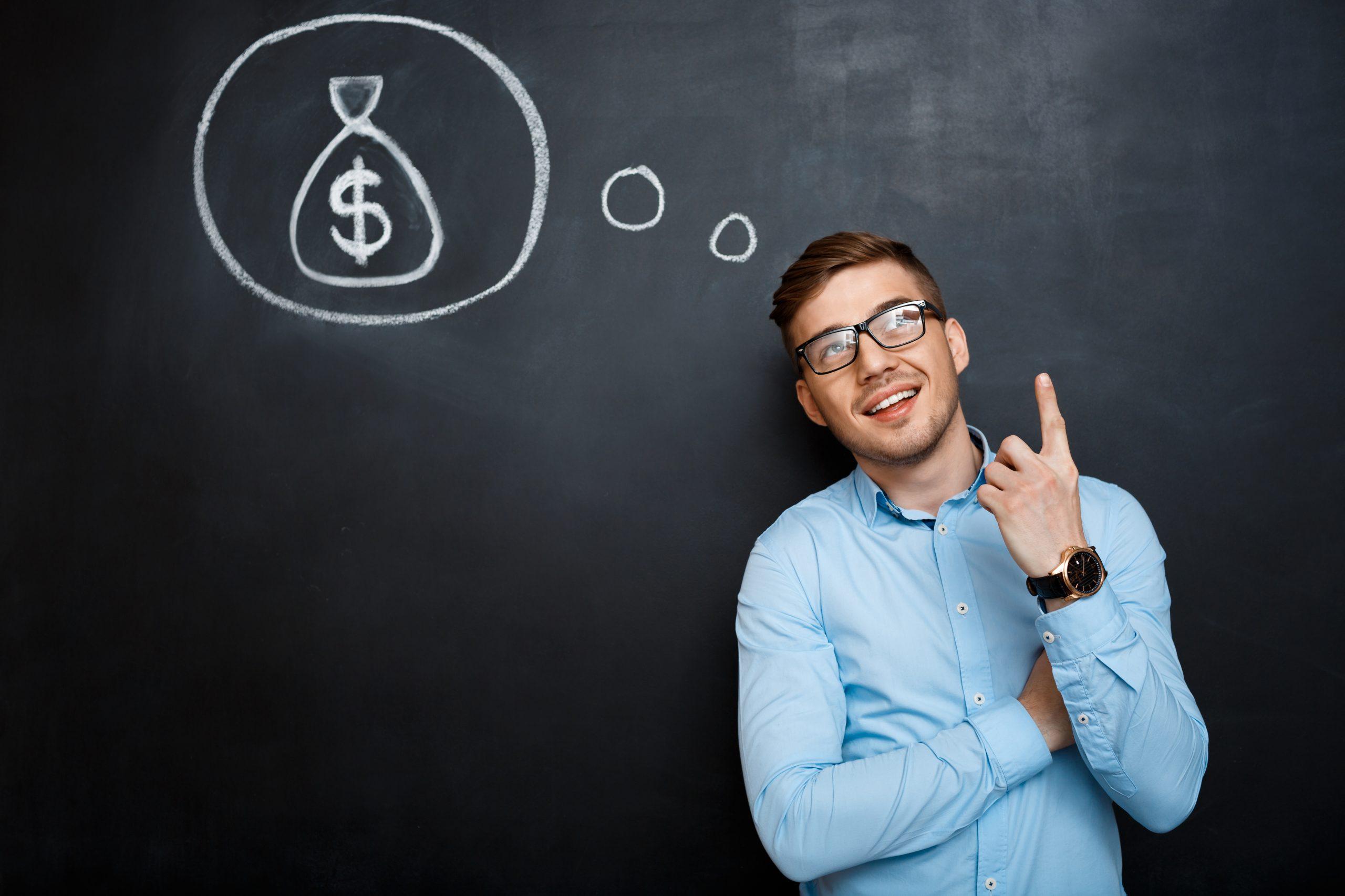 Portrait of minded, suited man standing crossed hands over blackboard. money concept